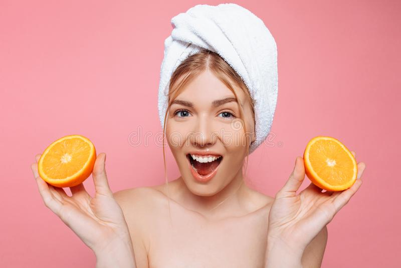 Portrait d'une femme gaie attirante avec une serviette enroulée autour de sa tête, tenant les tranches oranges au-dessus du fond  image stock