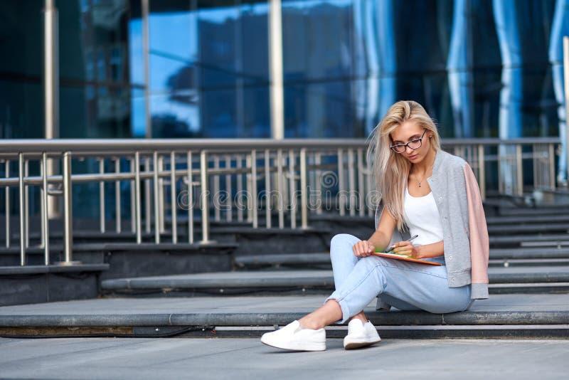 Portrait d'une femme heureuse attirante s'asseyant sur des escaliers ? la rue de ville photographie stock