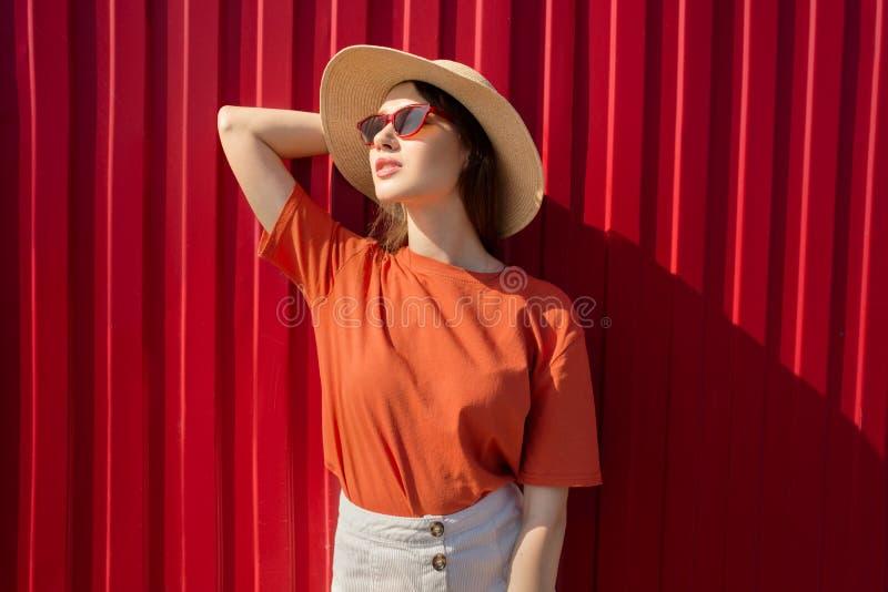 Portrait d'une femme heureuse face à son mur rouge Sourire naturel Jour ensoleillé photo stock