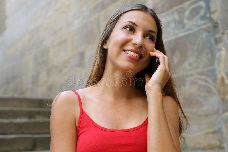 Portrait d'une femme heureuse parlant avec un téléphone portable dans une vieille ville image stock