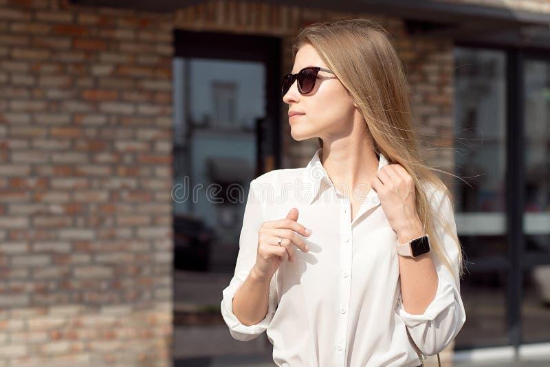 Portrait d'une femme heureuse r?ussie d'affaires dans une chemise blanche et des lunettes de soleil La montre intelligente sur un photographie stock