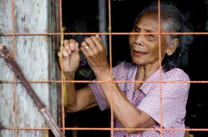 Portrait d'une femme indigène de village regardant de la fenêtre de la maison en bois photographie stock libre de droits