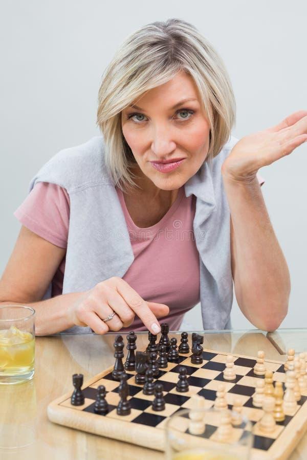 Portrait d'une femme jouant des échecs à la table images stock
