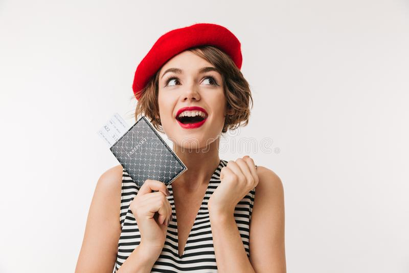 Portrait d'une femme joyeuse utilisant le béret rouge tenant le passeport images libres de droits