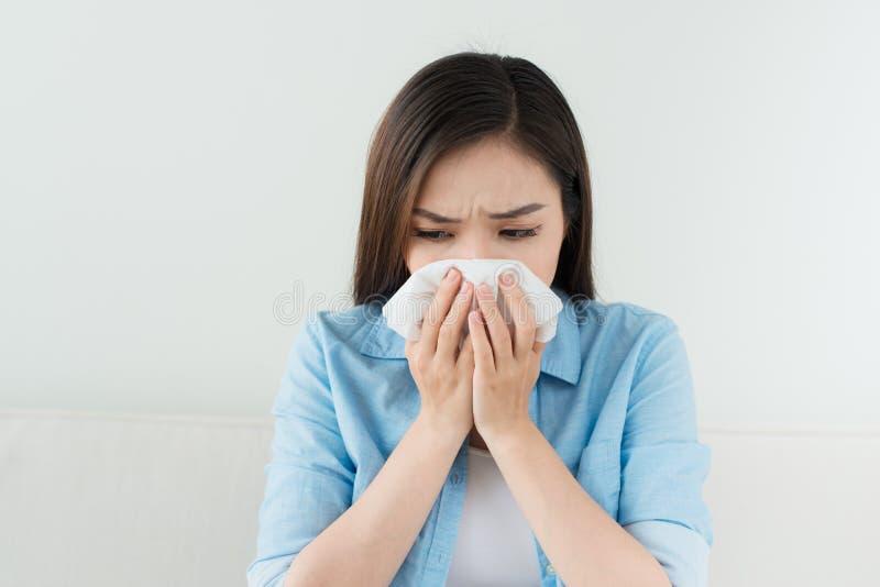 Portrait d'une femme malade soufflant son nez tout en se reposant sur le s photos stock