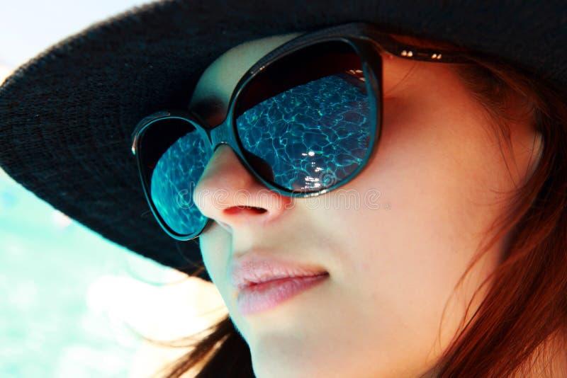 portrait d'une femme mignonne dans des lunettes de soleil images stock