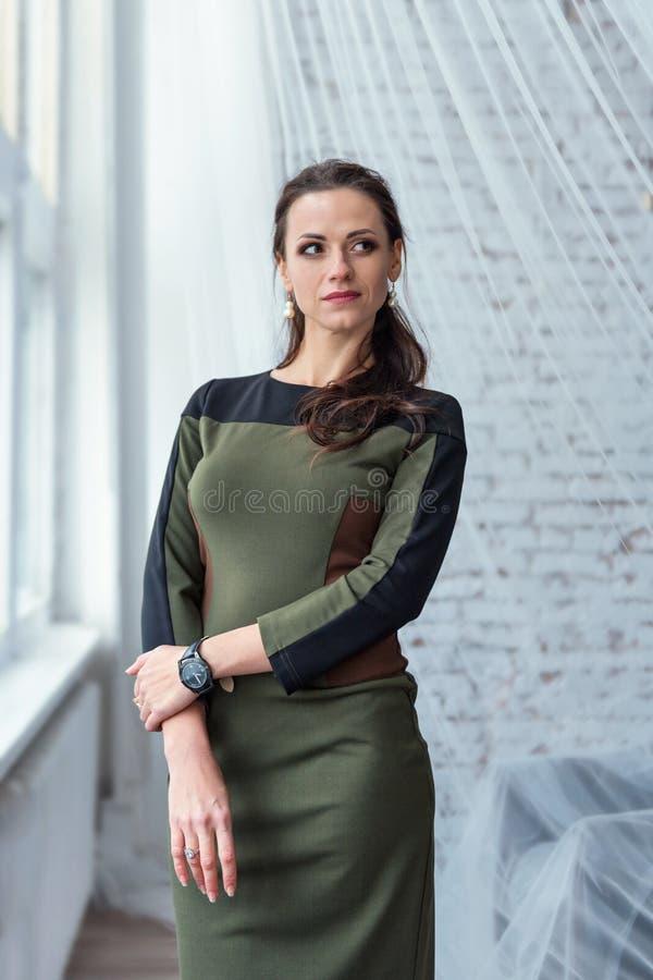 Portrait d'une femme mince attirante de brune dans une robe d'affaires se tenant prêt la fenêtre derrière un rideau transparent b photo stock