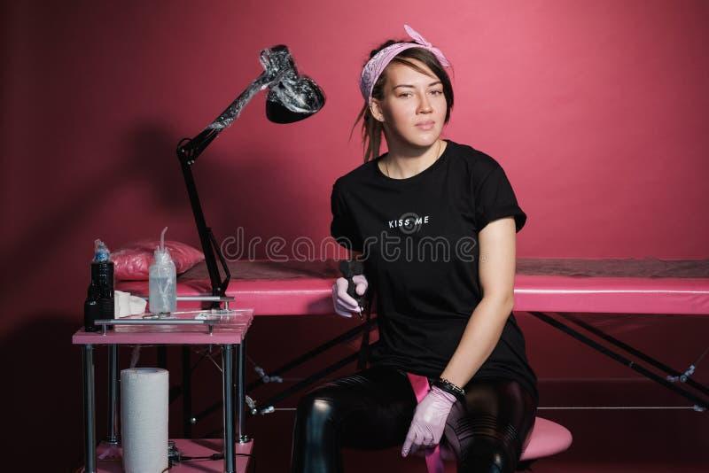 Portrait d'une femme professionnelle de maître de tatouage Vêtements noirs, et dreadlocks blanc rouge-rose de fond Endroit de photos stock