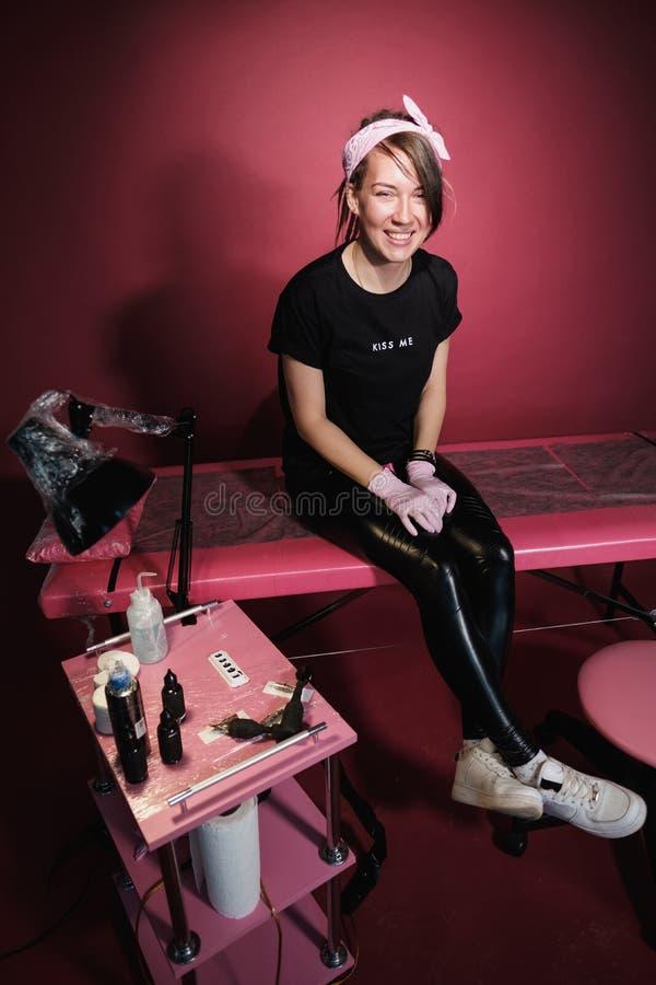 Portrait d'une femme professionnelle de maître de tatouage Vêtements noirs, et dreadlocks blanc rouge-rose de fond Endroit de photo stock