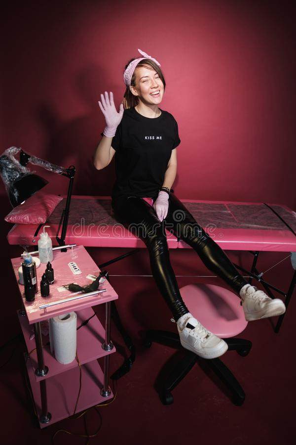 Portrait d'une femme professionnelle de maître de tatouage Vêtements noirs, et dreadlocks blanc rouge-rose de fond Endroit de photo libre de droits