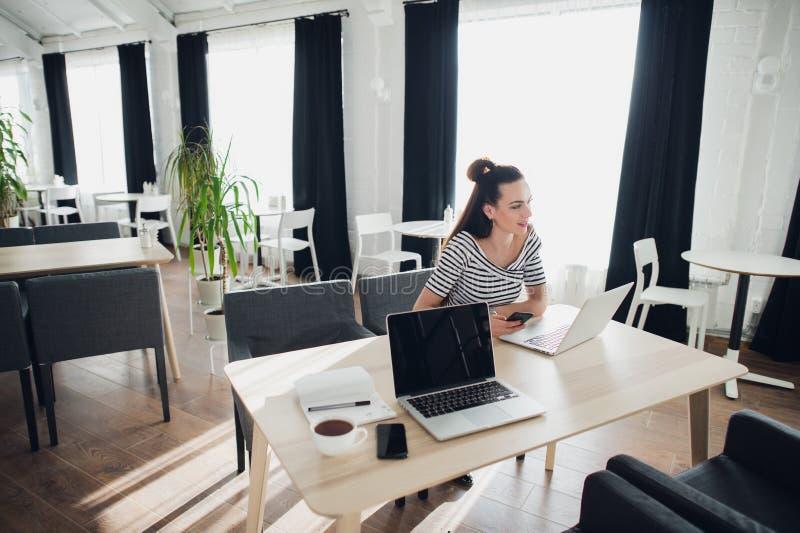 Portrait d'une femme réfléchie s'asseyant devant un ordinateur portable dans un café et regardant loin photographie stock