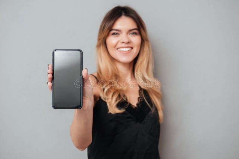 Portrait d'une femme sûre montrant le téléphone portable d'écran vide image libre de droits