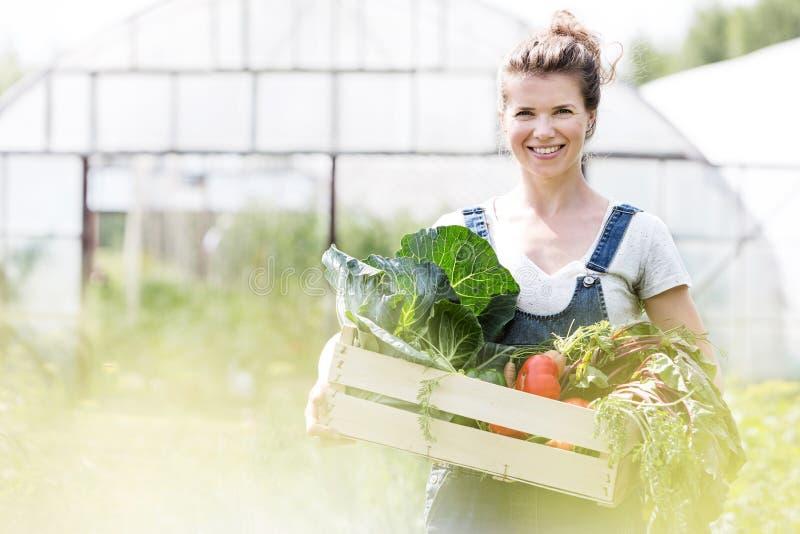 Portrait d'une femme souriante tenant des légumes en caisse à la ferme avec la lentille jaune en arrière-plan photo libre de droits