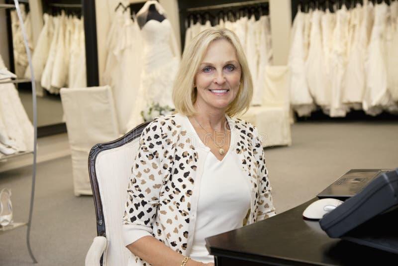 Portrait d'une femme supérieure heureuse s'asseyant dans le magasin nuptiale photo libre de droits