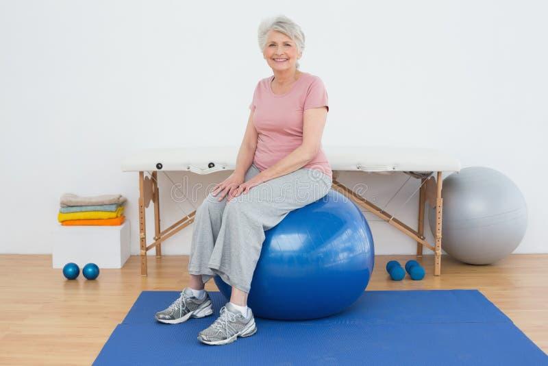 Portrait d'une femme supérieure s'asseyant sur la boule de forme physique photos stock