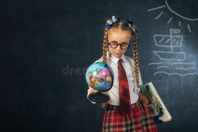 Portrait d'une fille d'école primaire avec un globe Uniforme scolaire photos stock