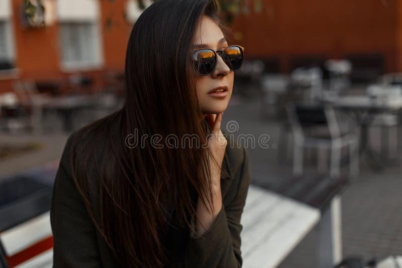 Portrait d'une fille élégante et jeune de brune utilisant un manteau vert et des lunettes de soleil, se reposant dehors image libre de droits