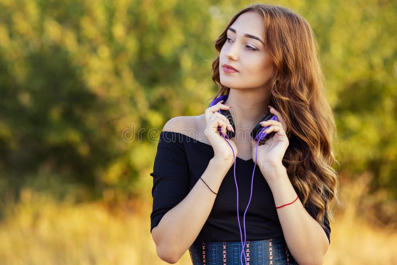 Portrait d'une fille d'adolescent de mélomane dans des écouteurs, jeune femme écoutant la belle chanson sur la nature dans le dom photo stock
