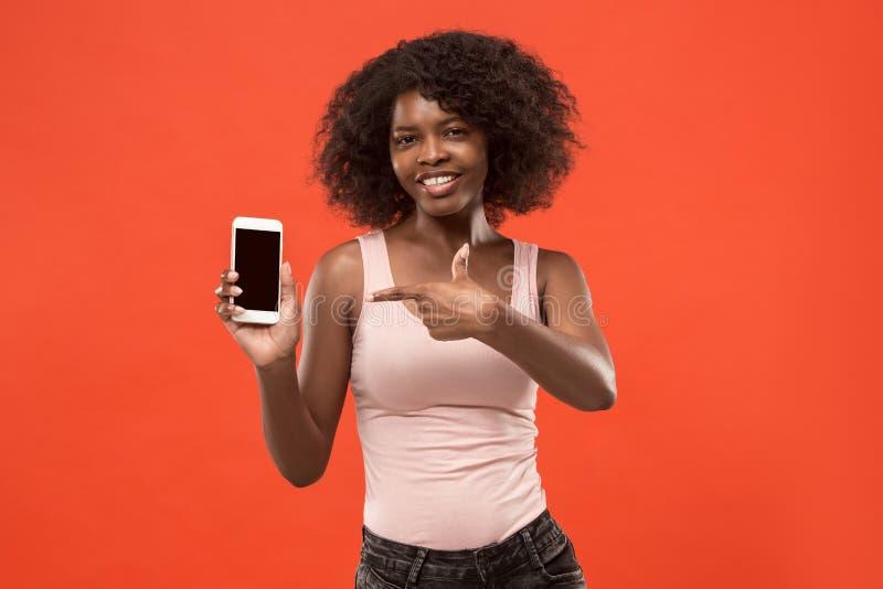 Portrait d'une fille Afro occasionnelle sûre montrant le téléphone portable d'écran vide d'isolement au-dessus du fond rouge images libres de droits
