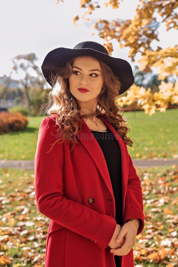 Portrait d'une fille aristocratique marchant en parc d'automne dans un manteau rouge et un chapeau noir photo stock