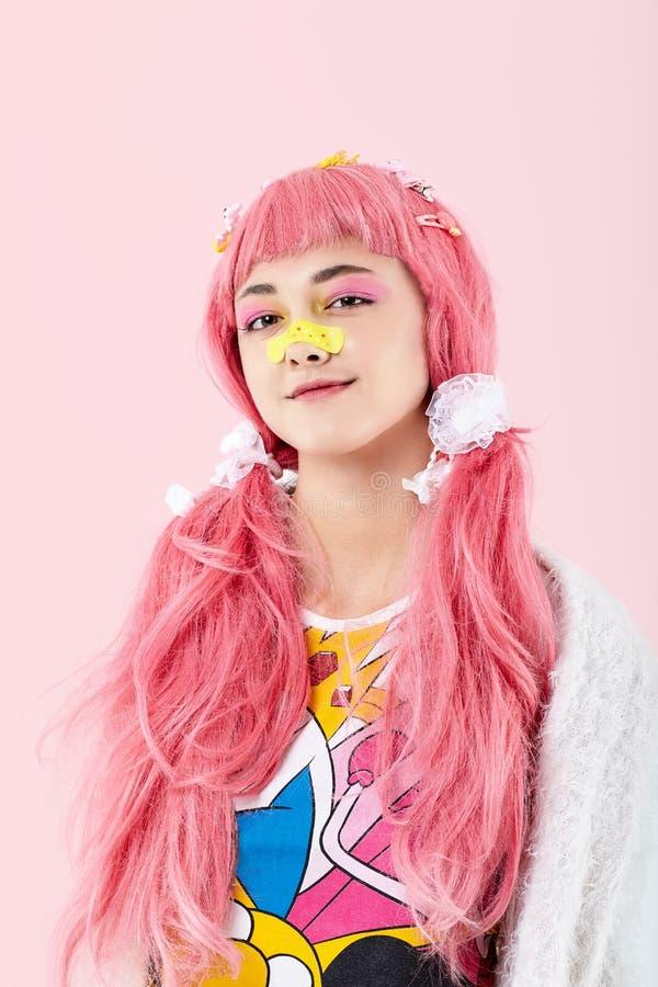 Portrait d'une fille asiatique dans une perruque rose dans un style de kawai photos libres de droits