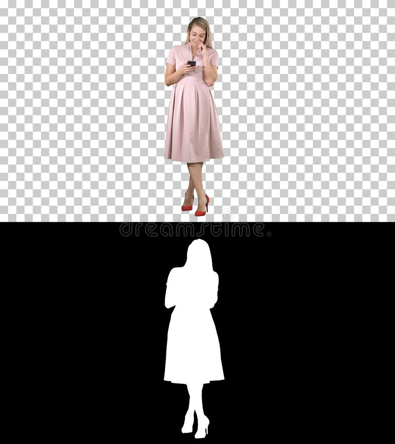 Portrait d'une fille assez de sourire dans des vêtements d'été utilisant le téléphone portable, message textuel, Alpha Channel photos stock