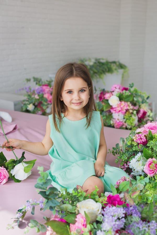 Portrait d'une fille assez petite dans une robe de turquoise près de fleurs dans un studio photographie stock