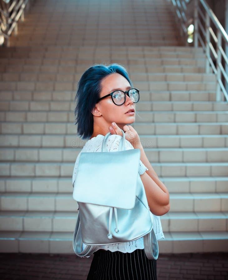Portrait d'une fille aux cheveux bleus attirante d'étudiant qui tient dans sa main un sac à dos avec le tissu argenté et la pose  image stock