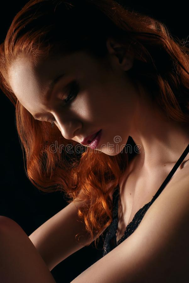 Portrait d'une fille aux cheveux bouclés rousse regardant vers le bas sur un fond noir image stock