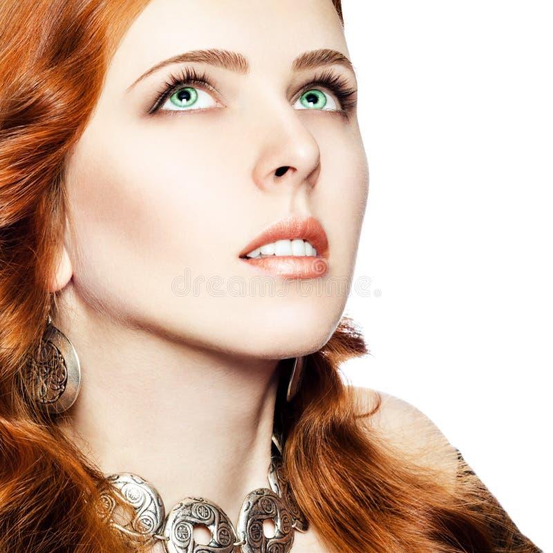 Portrait d'une fille aux yeux verts rousse en bijoux avec un ornement ethnique images libres de droits