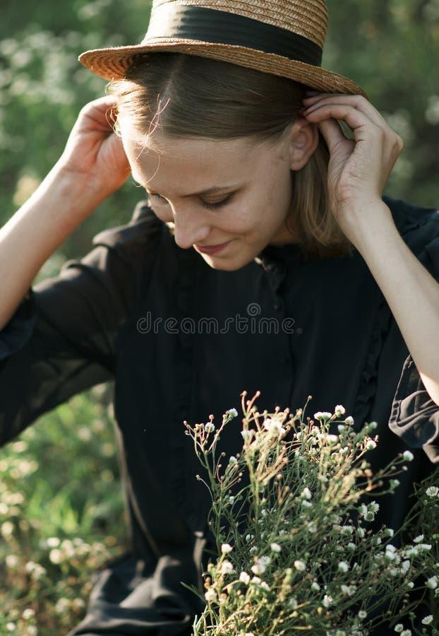 Portrait d'une fille avec du charme dans un chapeau de paille sur le champ images stock