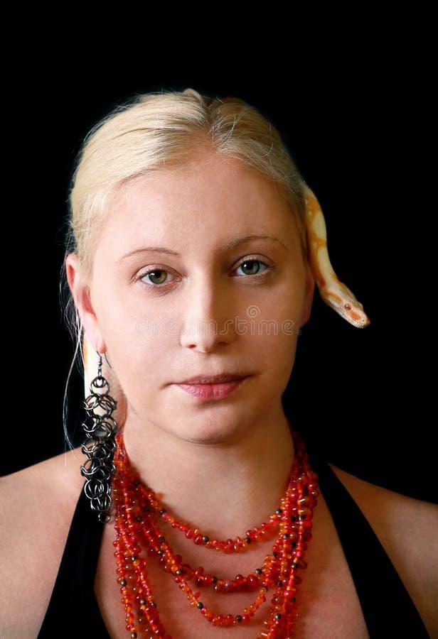 Portrait d'une fille avec le serpent albino Boa constrictor sur la tête Une femme avec bijoux, collier et oreilles pose devant la photo stock