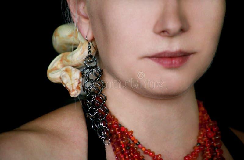 Portrait d'une fille avec le serpent albino Boa constrictor sur la tête Une femme avec bijoux, collier et oreilles pose devant la photos stock