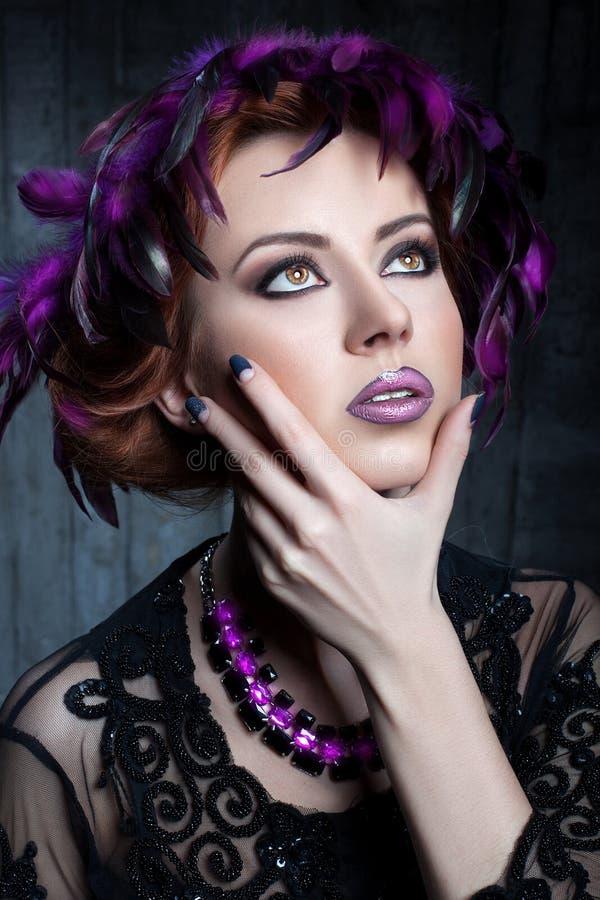Portrait d'une fille avec les plumes colorées dans ses cheveux photo stock