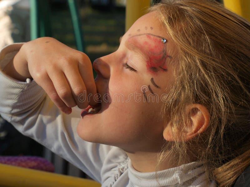 Portrait d'une fille avec une peinture de visage sur son visage mangeant une guimauve photo stock