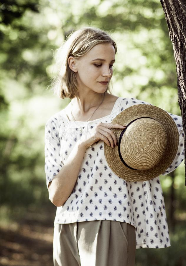 Portrait d'une fille avec un chapeau de paille dans des mains image stock