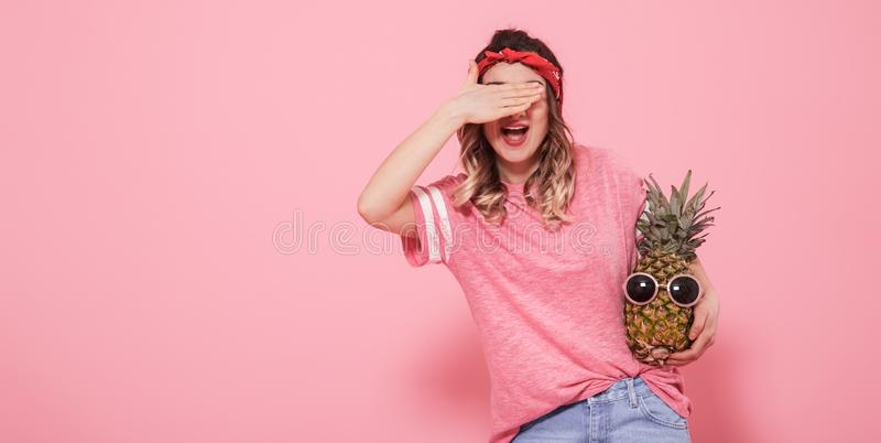 Portrait d'une fille avec un oeil fermé sur un fond rose images stock