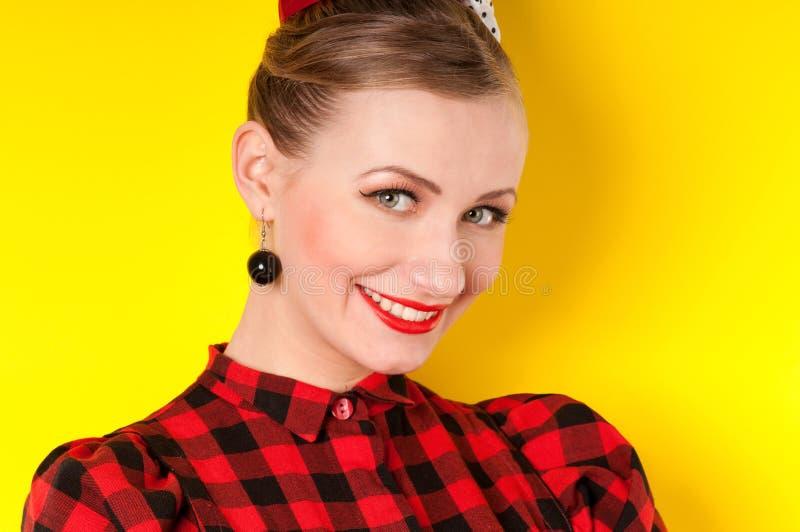 Portrait d'une fille avec un sourire sur un fond jaune dans rétro image libre de droits
