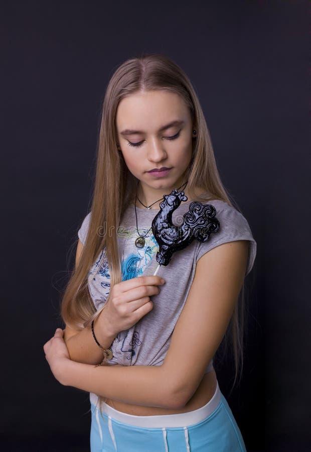Portrait d'une fille avec une lucette sur un fond noir photo stock