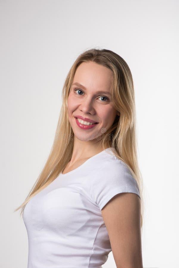 Portrait d'une fille blonde avec les yeux bruns dans des lentilles de contact souple bleues sur un fond blanc photo stock