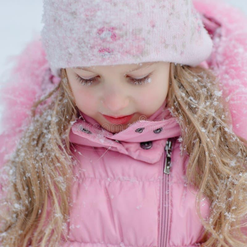 Portrait d'une fille blonde dans une veste rose sur un fond clair image libre de droits