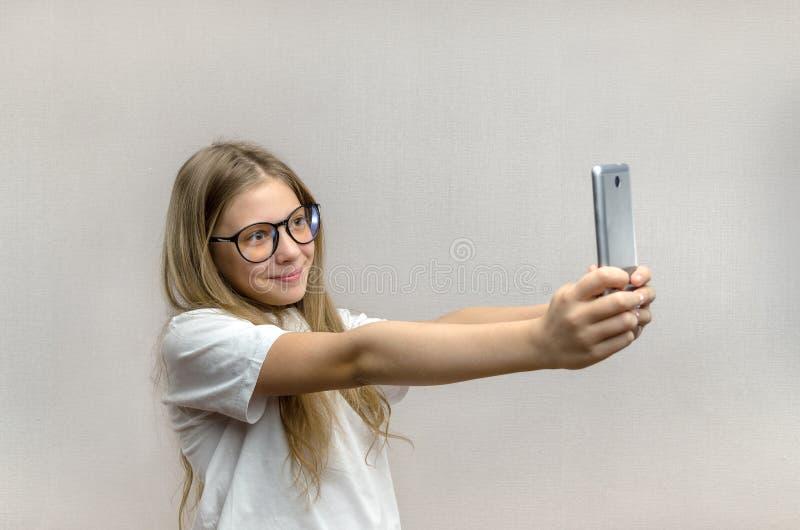 Portrait d'une fille blonde qui prend un selfie sur son smartphone Technologies modernes Jeune blogger images stock