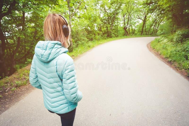 Portrait d'une fille blonde sportive attirante de nouveau à la lumière fonctionnant en bas de la veste, écouteurs de port de blue photo stock