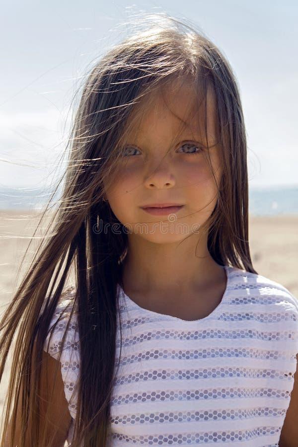 Portrait d'une fille bronzée sur la plage sablonneuse photo stock