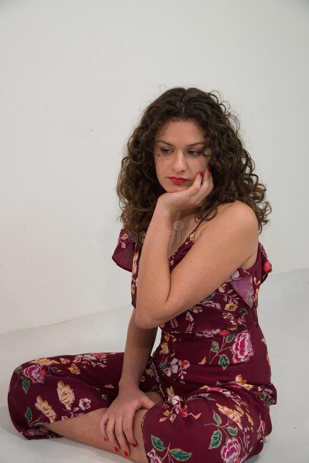 Portrait d'une fille d'une chevelure onduleuse et bouclée avec la robe sans bretelles fleurie, femme de mode image stock