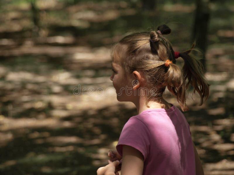Portrait d'une fille courante dans un T-shirt rose et avec deux queues sur sa tête  photo stock