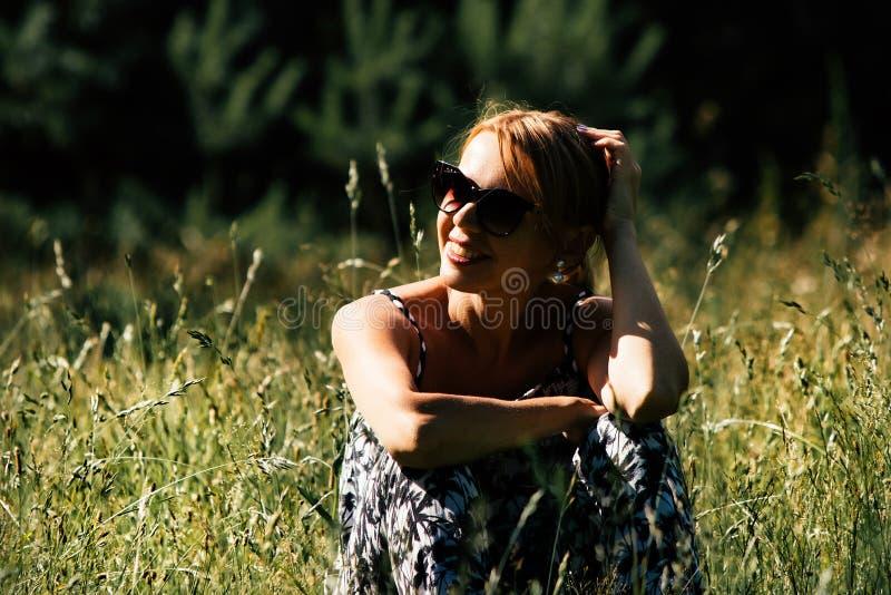 Portrait d'une fille dans des lunettes de soleil au pré photo stock