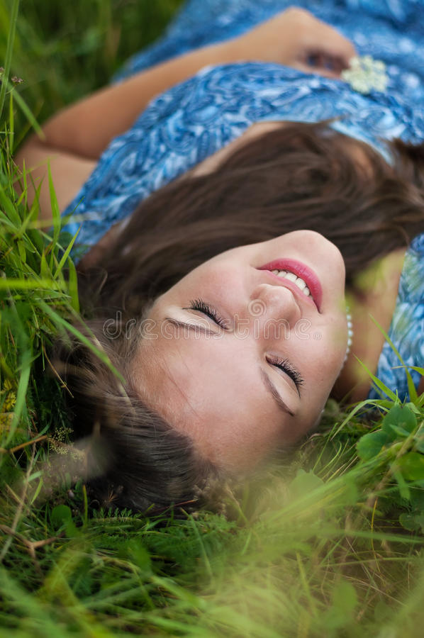 Portrait d'une fille dans l'herbe photo stock