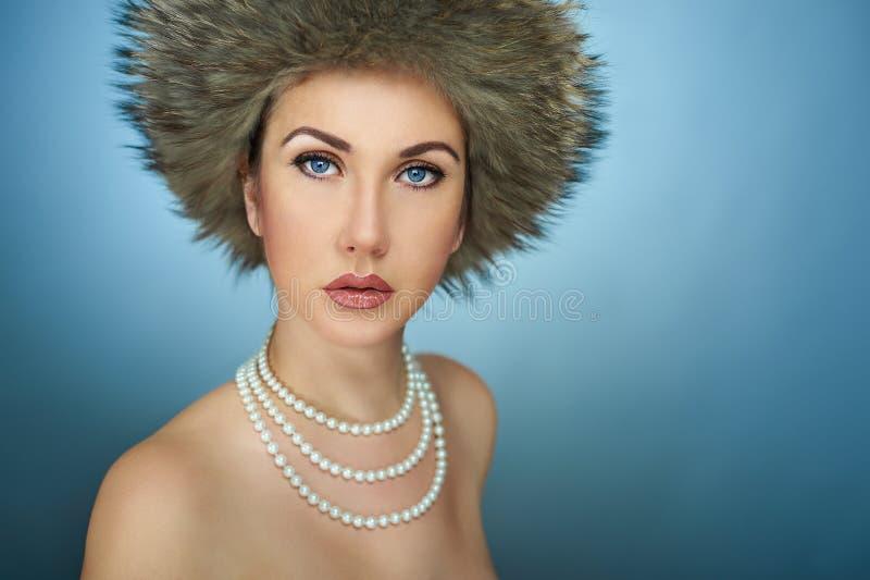 Portrait d'une fille dans le chapeau d'hiver dans le studio sur un fond bleu image stock