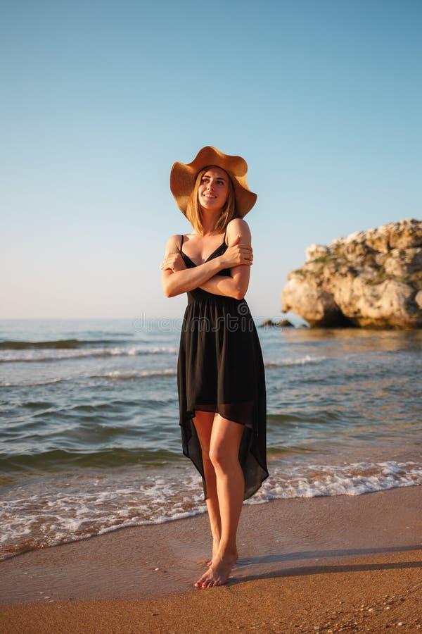 Portrait d'une fille dans une robe et un chapeau noirs sur la plage photos stock